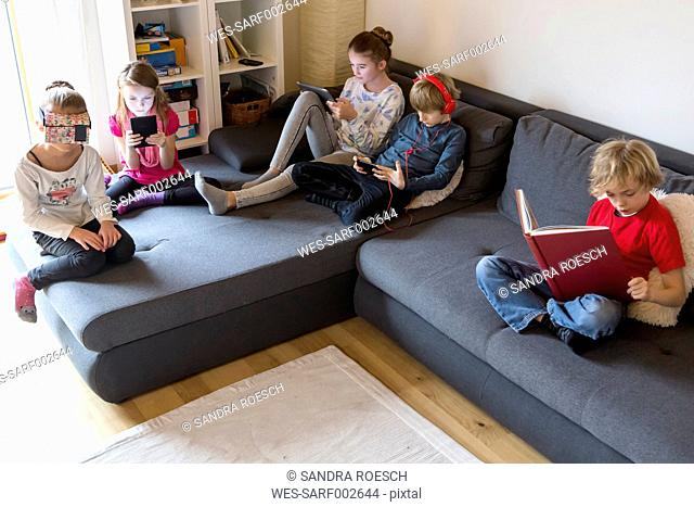 Four children on a couch using different digital devices while one boy reading a book
