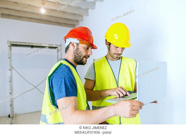 Workers using laptop at construction site