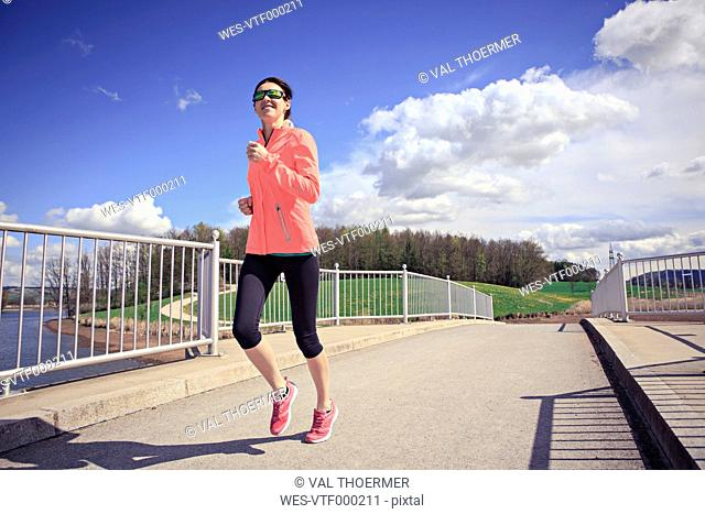 Woman jogging over a bridge