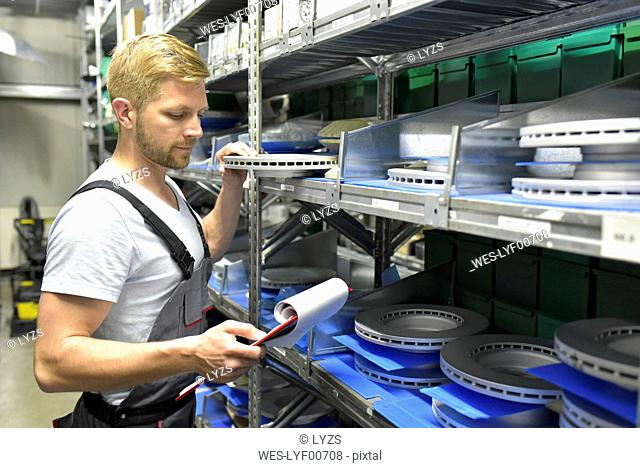 Man in warehouse looking at clipboard