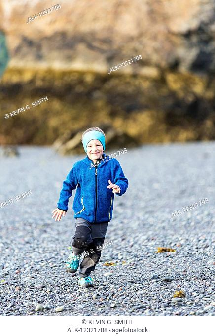 Young boy running on the beach, Hesketh Island, Southcentral Alaska, USA