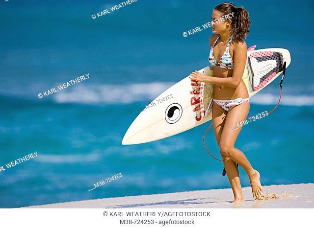 Girl holding surf board, Oahu, Hawaii, USA