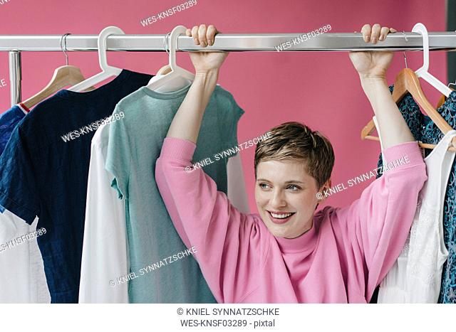 Portrait of smiling woman at clothes rail