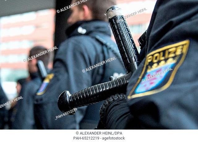 A police officer with a night stick secures with colleagues from police task force the premises at the Higher Regional Court inFrankfurt am Main,Germany