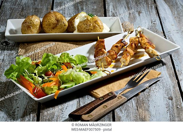 Chicken meat sticks with baked potatoes and mixed salad
