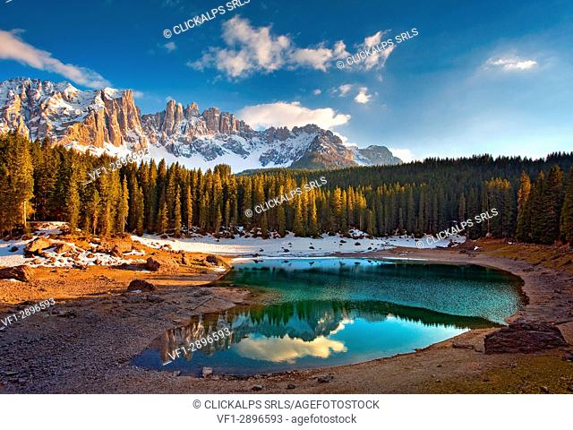 Dolomites. The Carezza lake, with fir forests and the Latemar ridge in the background, at sunset