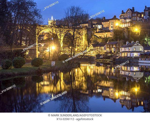Viaduct and Waterside buildings reflected in the River Nidd at dusk Knaresborough North Yorkshire England