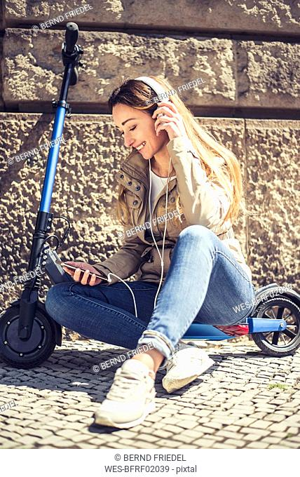 Happy woman sitting on E-Scooter listening music with headphones and smartphone