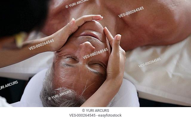 Top view of a senior man receiving a relaxing facial and head massage