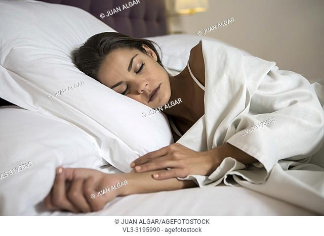 Beautiful young brunette under white blanket lying on soft pillow in bed and sleeping