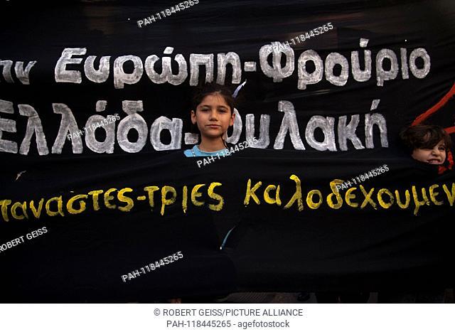 "Refugee children with their heads through banner. Writing """"Europe - Fortress Greece - Prison"""". 16.03.2019 | usage worldwide. - Athen/Greece"