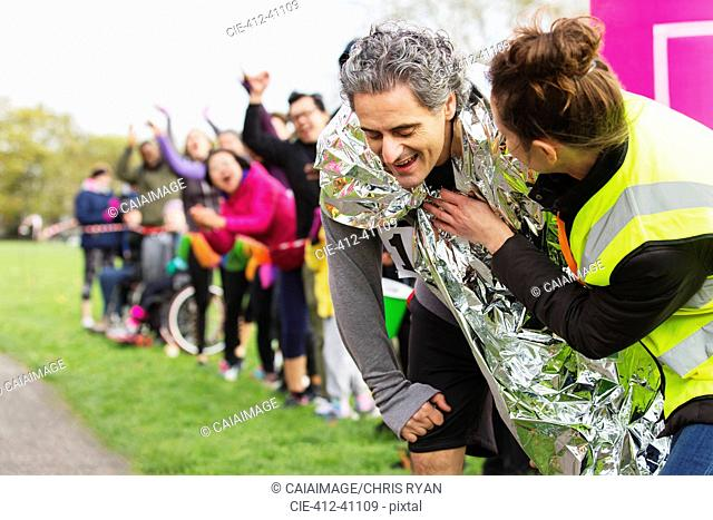 Woman wrapping thermal blanket around exhausted male runner finishing marathon