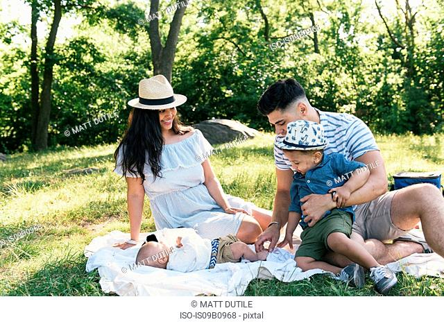 Parents and toddler looking at baby son on picnic blanket in Pelham Bay Park, Bronx, New York, USA
