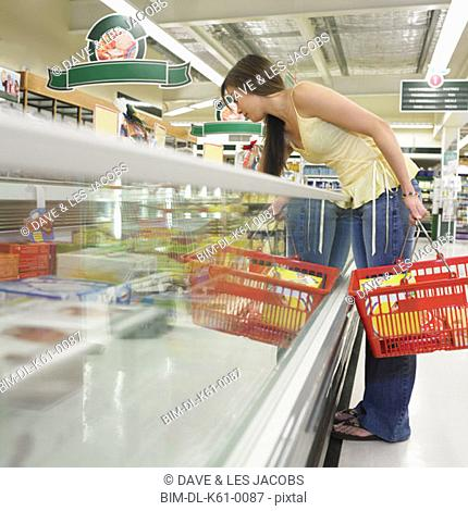 Woman selecting frozen food at supermarket, Perth, Australia