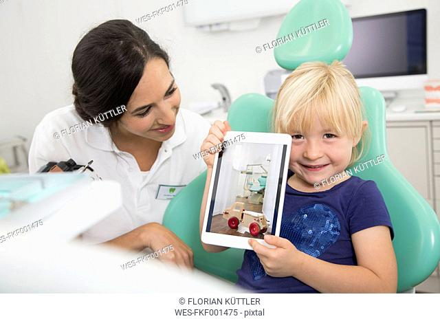 Dentist and smiling girl showing digital tablet in dentist's chair