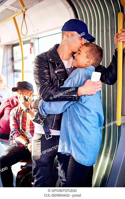 Romantic young couple hugging on city tram