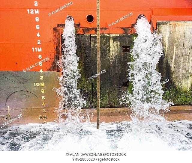 Large merchant ship emptying ballast water in Puerto de La Luz, Las Palmas, Gran Canaria, Canary, Islands, Spain
