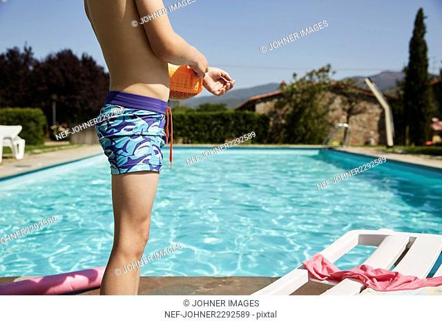 Boy next to a swimmingpool