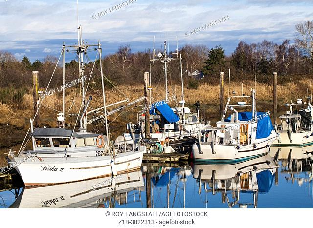 Commercial fishing boats moored in a narow channel at Steveston, British Columbia. Canada