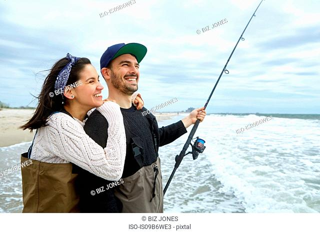 Young couple in waders sea fishing