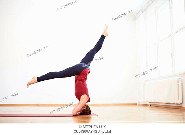 Woman in exercise studio legs apart doing headstand