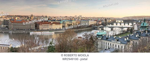 Panorama of the historical bridges and buildings reflected on Vltava River at sunset, Prague, Czech Republic, Europe