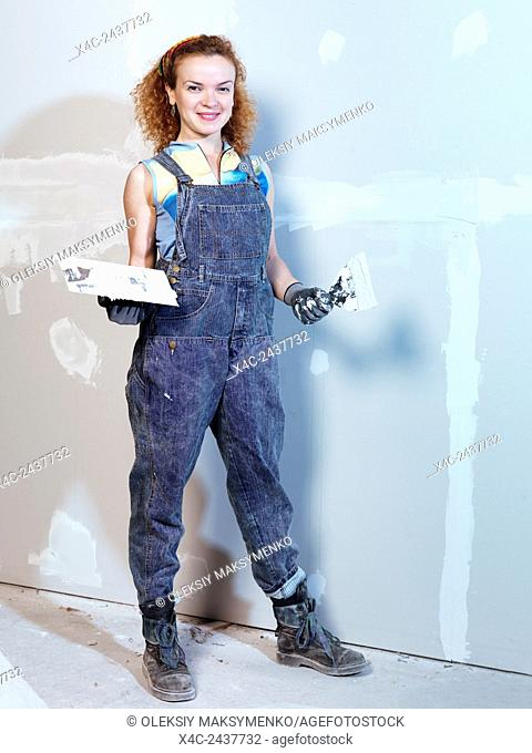 Portrait of a smiling young woman construction worker with a trowel and putty knife patching up drywall