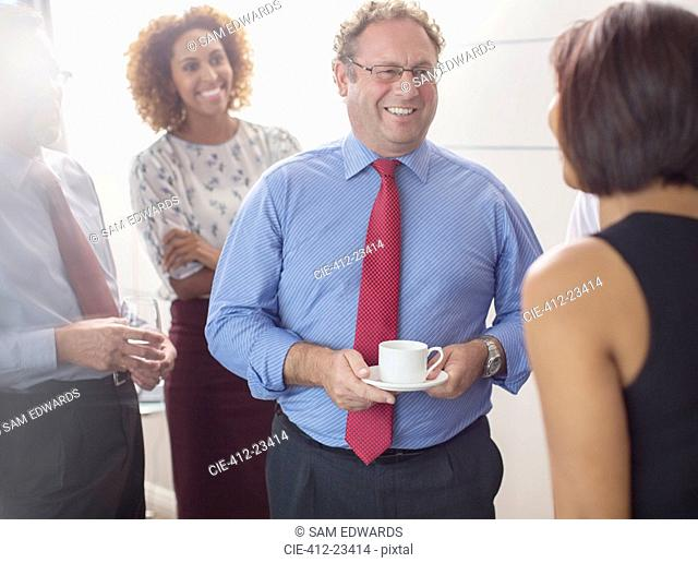 Businessman talking to colleagues in office and holding coffee cup