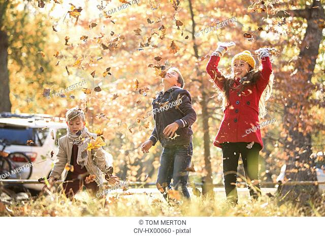 Boys and girl throwing autumn leaves overhead