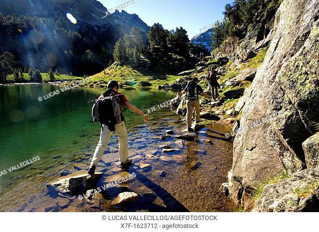 Trippers in Redon lake,Colomèrs cirque,Aran Valley, Aigüestortes and Estany de Sant Maurici National Park,Pyrenees, Lleida province, Catalonia, Spain