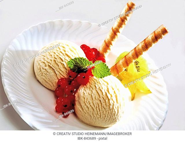 Two scoops of vanilla ice cream with fruit and wafers