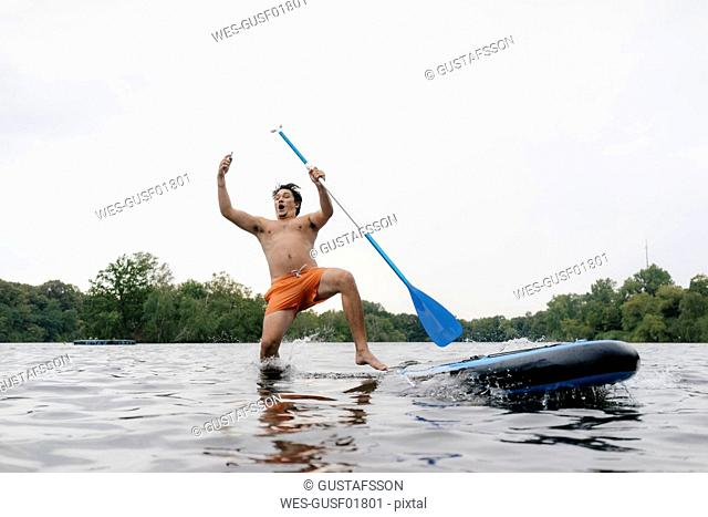 Man falling from SUP board while taking a selfie