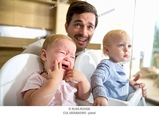 Father between male and female twin toddlers in high chairs
