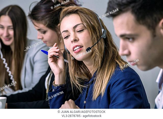 Young woman sitting and communicating in the call center during the work. Horizontal indoors shot