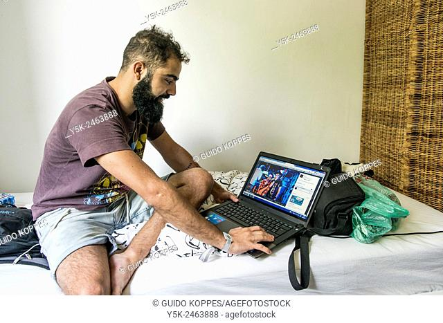 Tilburg, Netherlands. Brazilian male traveller sitting on the bed of his Airbnb guest room with his laptop computer at arms length