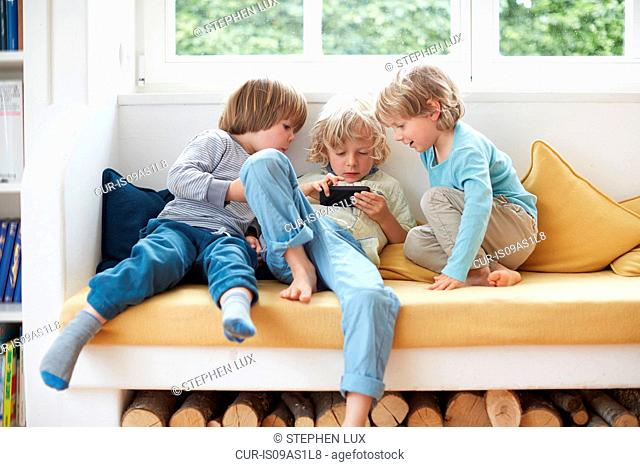Three boys shitting on window seat together looking at smartphones