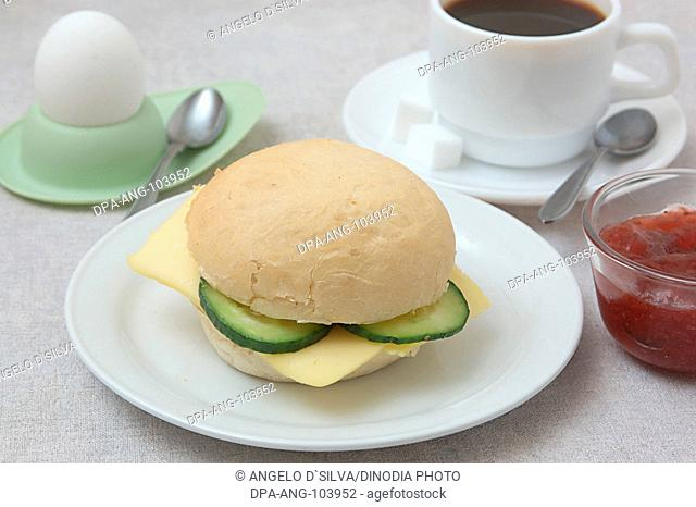 Food , Bread roll with cheese and cucumber , boiled egg on egg holder and spoon , cup of coffee , sugar cubes , strawberry jam