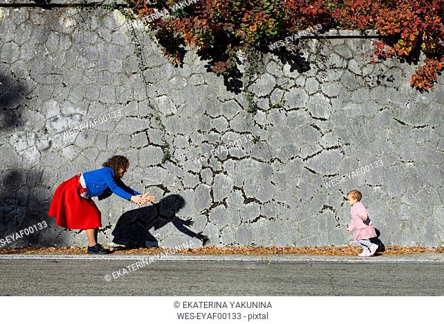 Little girl running to her mother at a stone wall