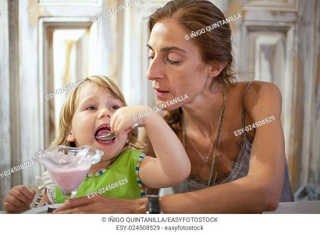 three years old child with green bib open big mouth eating strawberry ice cream with spoon from crystal cup next to mother at restaurant