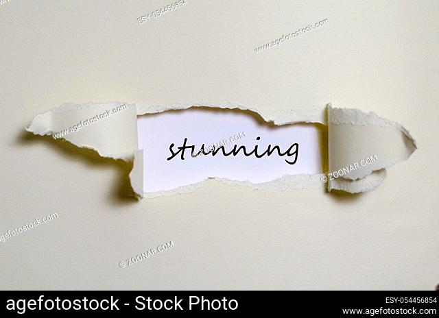 The word stunning appearing behind torn paper