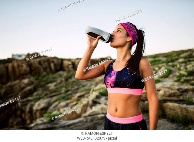 Portrait of an athlete woman drinking water outdoors