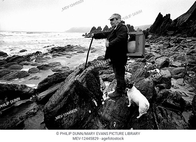 A beachcomber with his pet Jack Russell dog on the beach at Marloes, Pembrokeshire, South Wales. He carries an old plastic stool and a boat fender he has found...