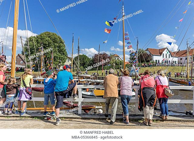 Wattensail, harbour celebration, visitors looking at decorated flat bottom sailship in the museum harbour of Carolinensiel