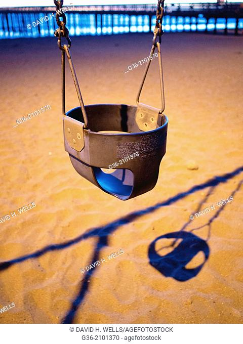 Empty baby swing and sand at beach in Cayucas, California, United States
