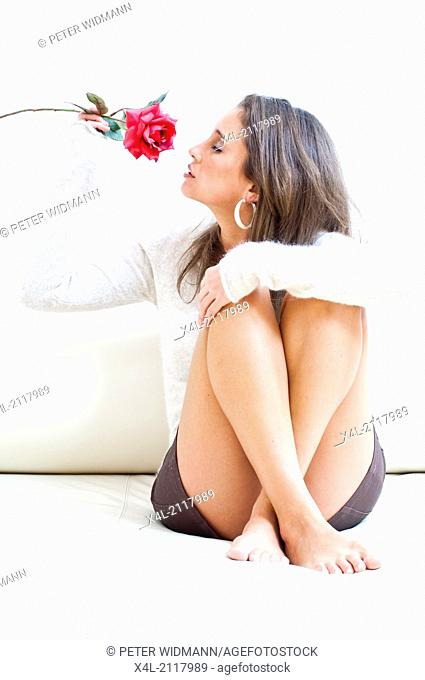 Young woman sitting on a couch, smelling a red rose (model-released)