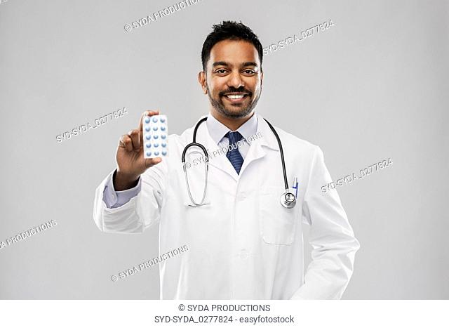 indian male doctor with pills and stethoscope