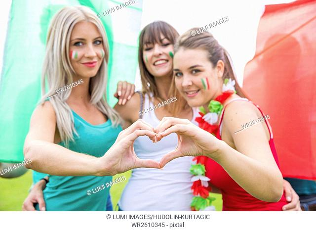 Female soccer fans forming heart with hands
