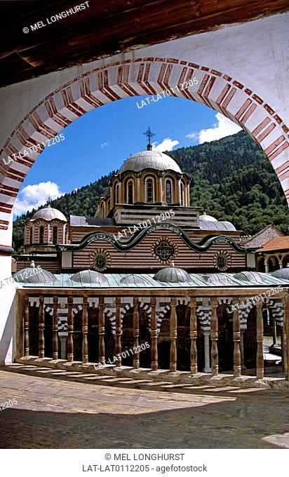 View of Nativity Church from balcony through arch. Rila Monastery. Domes. Coloured brickwork. Tower. Decorated stonework