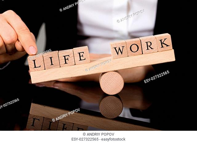 Close-up Of A Person Showing Imbalance Between Life And Work On Seesaw