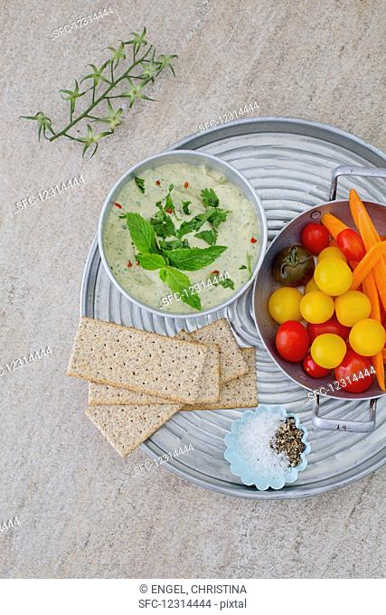 Herb houmous on a tray with colourful tomatoes and crispbread
